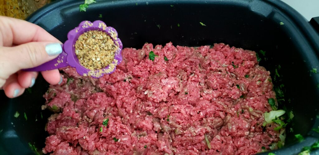 raw ground beef in a crockpot with a hand pouring seeds into the meat