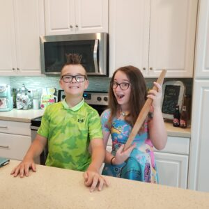 2 kids standing in a kitchen with a rolling pin