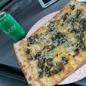 pizza on a platewith a bubly lime next to it