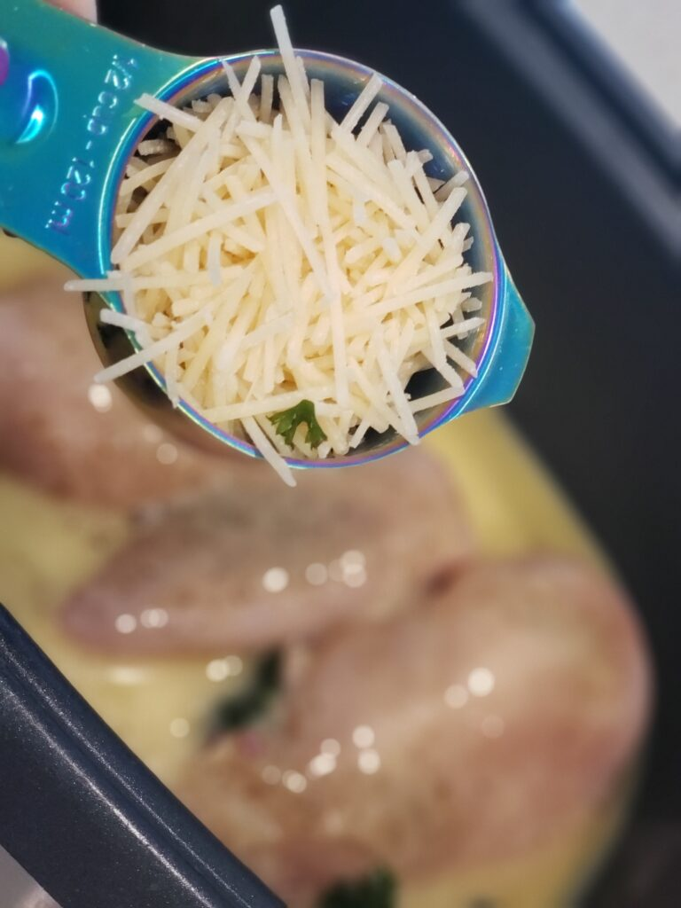 parmesan cheese in a cup over crockpot of chicken