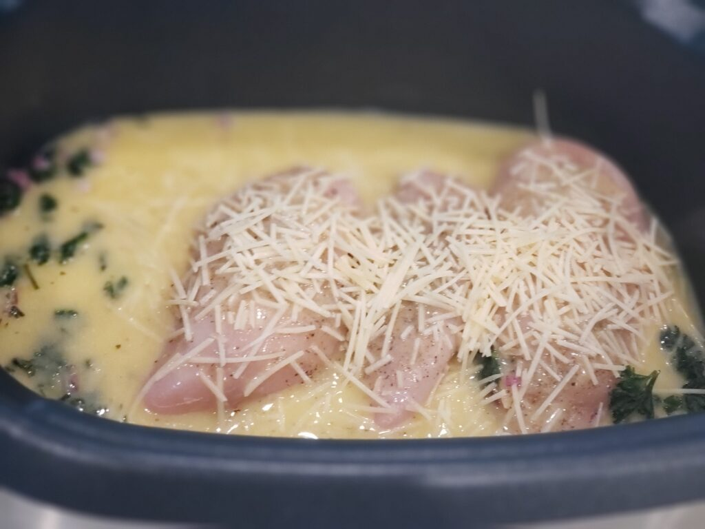 crockpot with chicken adn cheese sprinkled on top