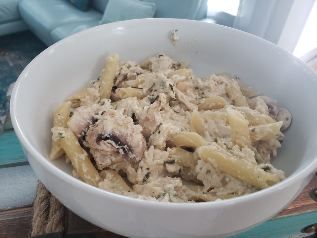 white bowl with penne pasta and creamy chicken with mushrooms