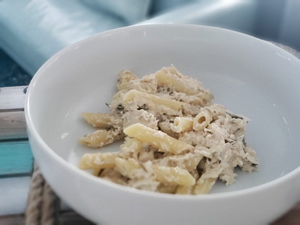 white bowl with penne pasta and creamy chicken