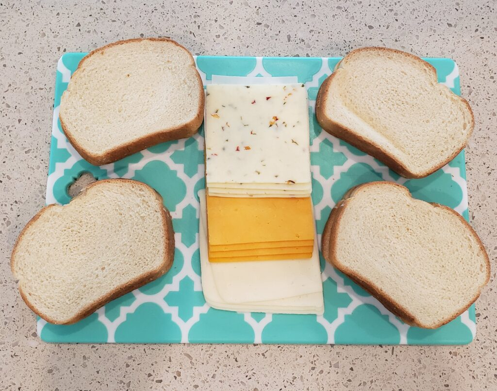 4 slices of bread on a cutting board with cheese in the middle