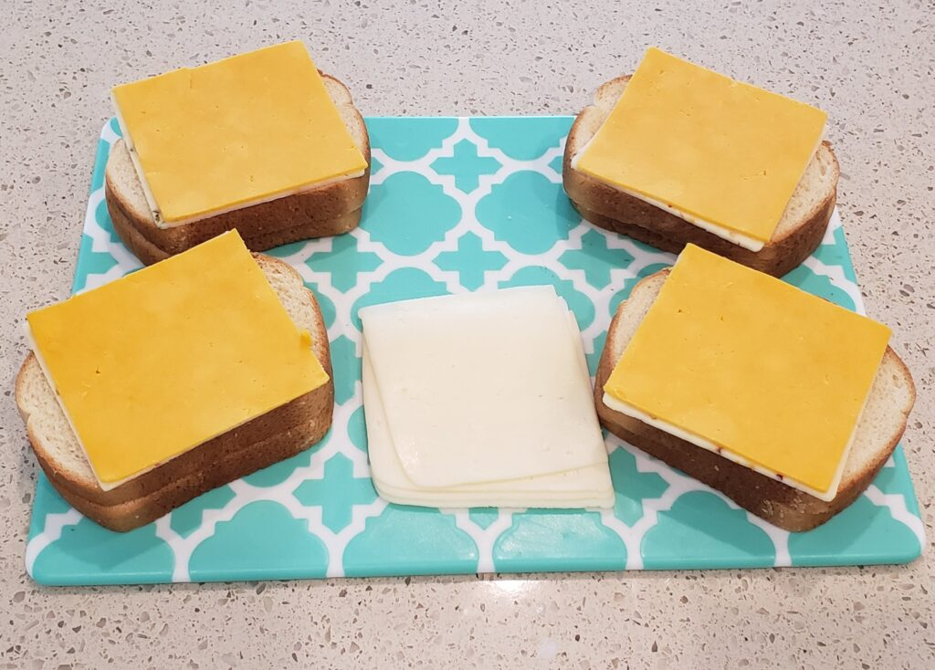 bread on a cutting board with 2nd slice of cheese on the bread