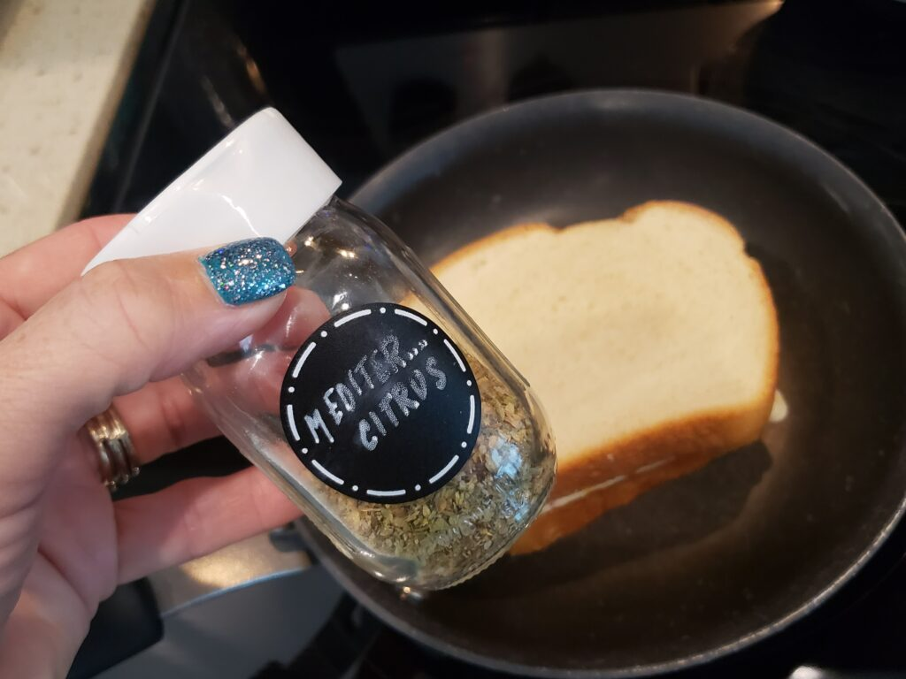 Mediterranean citrus spices in a jar in a womans had over a pan with grilled cheese in it