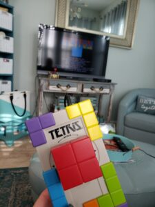 tetris in a hand in front of the tv